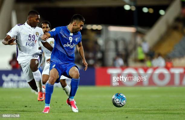 Esteghlal's Kaveh Rezaie fights for the ball agaisn alAin's Saeed Juma during the 2017 AFC Champions League round 16 football match between Iran's...