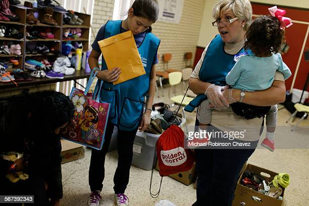 Estela Gonzalez, right, and her daughter Mikaela, center, assist Maria Castro, left and her 2-year-old daughter Natalia Maravillaga. Castro and her...