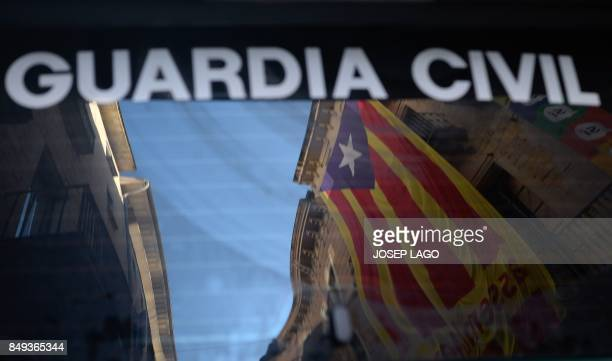 A 'Estelada' is reflected on the window of a Spanish Civil Guard car in front of the headquarters of the company of waters of Girona on September 19...