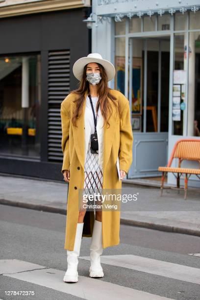 Estelle Chemouny seen wearing hat, beige coat, skirt, white boots, blazer, micro Prada bag outside Paco Rabanne during Paris Fashion Week -...