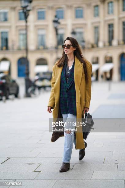 Estelle Chemouny wears a beige / pale brown long wool coat, a blue and white checked oversized blazer jacket, a white t-shirt, a black leather...