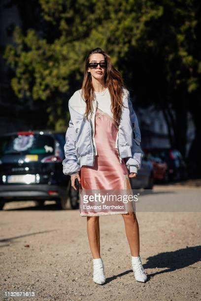 Estelle Chemouny wears a bomber jacketa pink silky dress white shoes sunglasses outside Unravel Project during Paris Fashion Week Womenswear...
