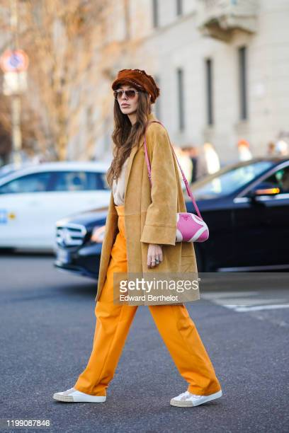 Estelle Chemouny wears a brown beret hat aviator sunglasses a beige suede coat a pink Prada bag orange pants Prada sneakers shoes outside MSGM during...