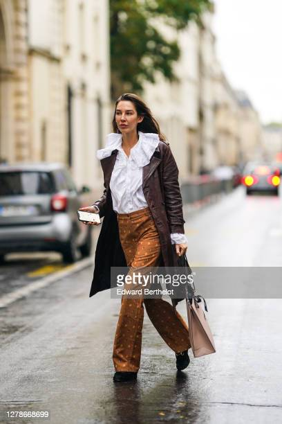 Estelle Chemouny wears a brown leather long jacket, a white ruffled collar shirt, orange flared pants with printed features, a Pale pink Fendi bag,...