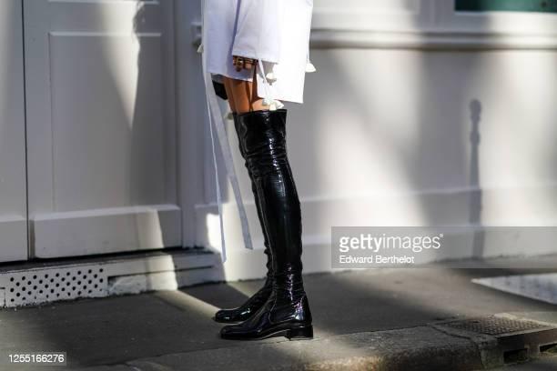 Estelle Chemouny wears a Charles Jeffrey oversized white long shirt/dress, a golden necklace, Prada thigh high black leather shiny boots, on July 08,...