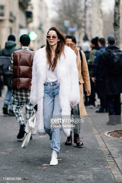 Estelle Chemouny wears a white fluffy coat, blue ripped jeans, white shoes, sunglasses, a white bag, outside Issey Miyake, during Paris Fashion Week...