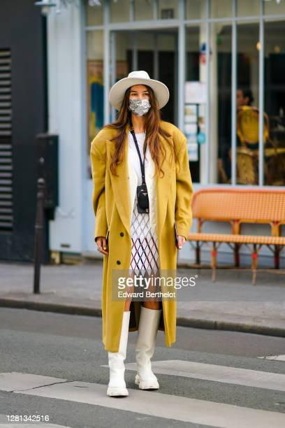 Estelle Chemouny wears a white hat, a mustard-yellow long oversized coat, a white jacket, a Prada small bag, a white and clear mesh dress with argyle...