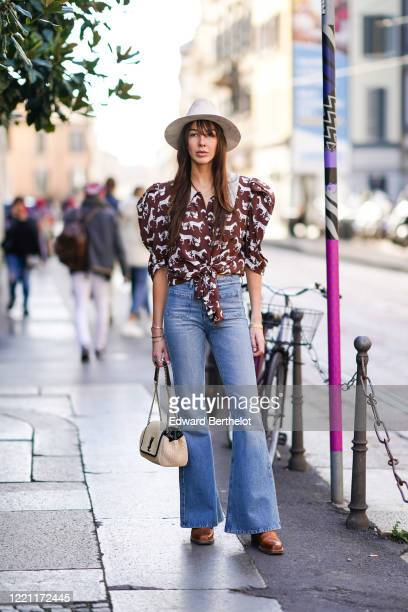 Estelle Chemouny wears a white hat a ruffled puff shoulders brown shirt with printed horses blue flare denim jeans pants a Saint Laurent YSL bag...