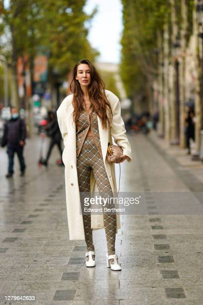Estelle Chemouny wears a white long coat a pale pink leather quilted Miu Miu bag a beige checkered cardigan leggings white shoes outside Miu Miu...