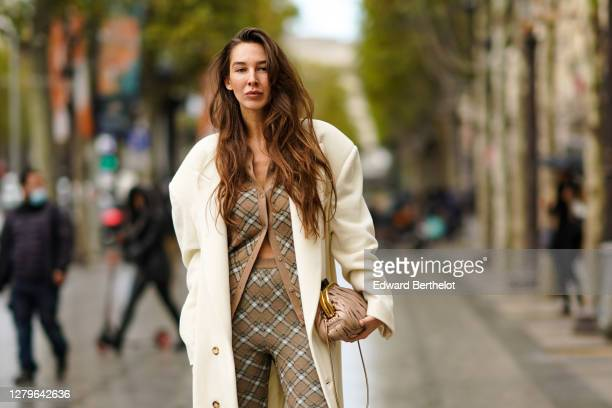 Estelle Chemouny wears a white long coat a pale pink leather quilted Miu Miu bag a beige checkered cardigan leggings outside Miu Miu during Paris...