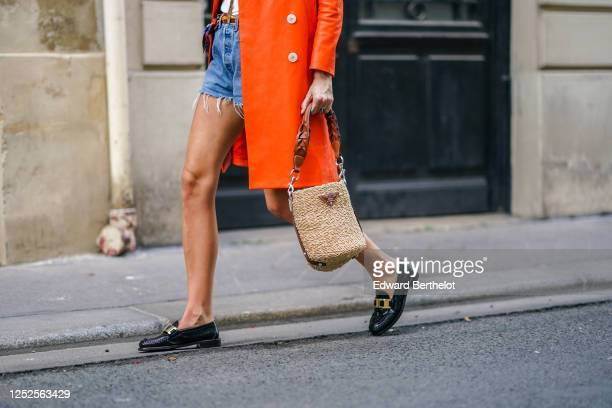 Estelle Chemouny wears a wooden / straw Prada bag, black leather Prada shoes, blue denim ripped shorts, an orange leather coat from Prada, on June...