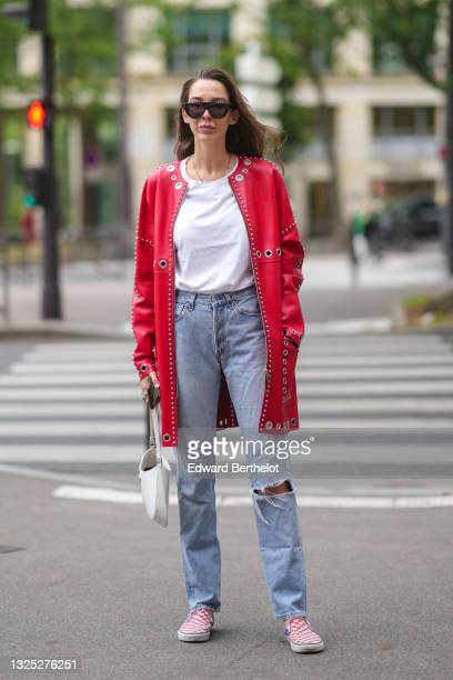 Estelle Chemouny wears black sunglasses, a gold chain necklace, a white t-shirt, a red shiny leather nailed / studded long jacket, blue faded denim...