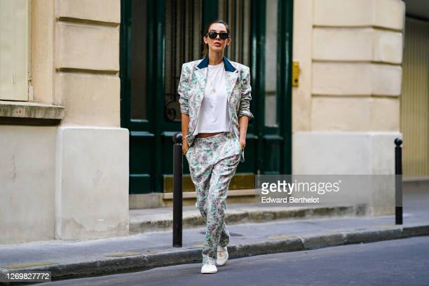 Estelle Chemouny wears pastel green / pink floral print suit from Charles Jeffrey for Paradise Garage Store, a golden necklace, a white t-shirt,...