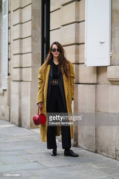 Estelle Chemouny wears Ray Ban sunglasses, a brown / khaki wool oversized long coat, a red Alaia leather bag, a black top, a dark gray oversized...