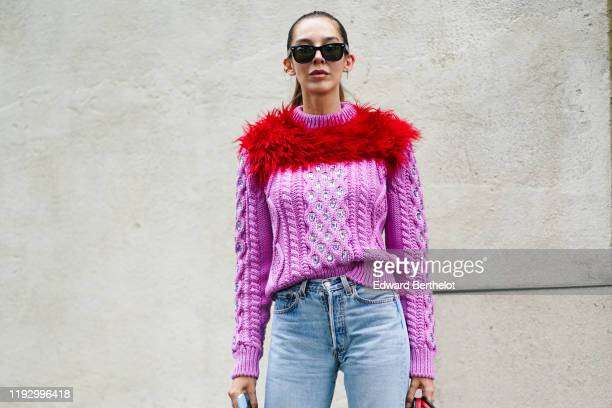 Estelle Chemouny wears sunglasses a pink knit sweater with a red fluffy decoration and glittering rhinestones blue denim pants outside the Prada show...