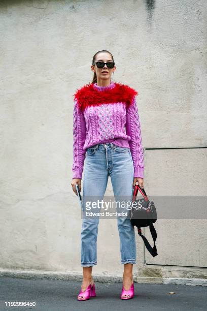 Estelle Chemouny wears sunglasses, a pink knit sweater with a red fluffy decoration and glittering rhinestones, blue denim pants with rolled-up hems,...