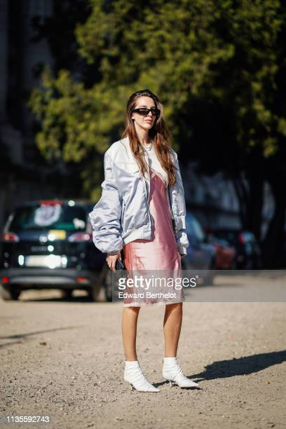 Estelle Chemouny wears sunglasses a shiny pink satin dress a shiny grey satin and white denim jacket white pointy ankle boots outside Unravel Project...