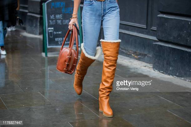 Estelle Pigault is seen wearing brown winter boots, denim jeans, brown bag outside Christopher Kane during London Fashion Week September 2019 on...