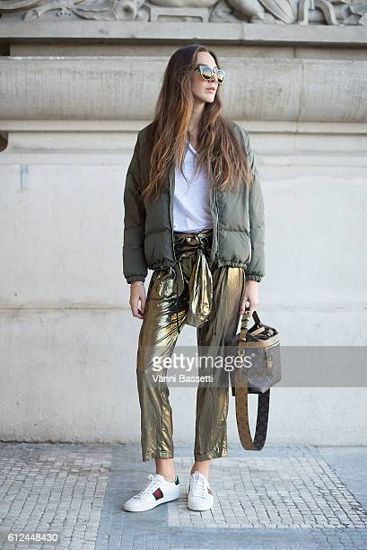 Estelle Pigault poses wearing a Sessun jacket Louis Vuitton bag and Gucci sneakers poses before the Shiatzy Chen show at the Grand Palais during...