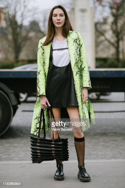 Estelle Pigault poses with a Y/Project bag and Prada stockings and shoes after the Ann Demeulemeester show at the Theatre National de Chaillot during...