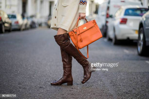 Estelle Pigault wearing brown military hat Loewe cardigan Prada tshirt brown Prada leather boots orange Hermes bag during London Fashion Week Men's...
