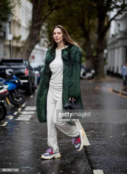 Estelle Pigault wearing green fake fur coat Zeynep Kartal creme jumpsuit Esau Yori Balenciaga Triple S sneaker black Balenciaga bag on October 18...