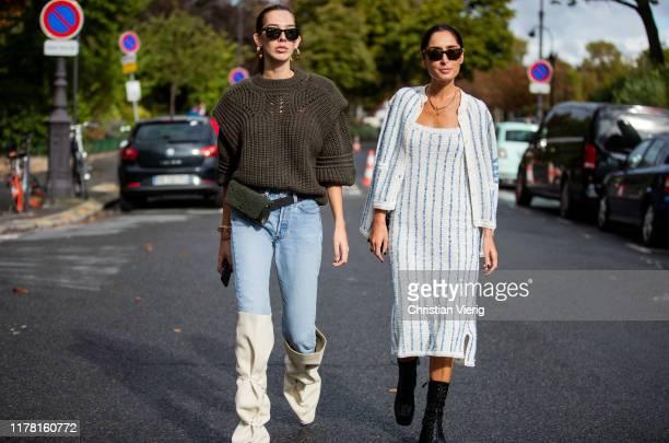 Estelle Pigault wearing olive knit, denim jeans, belt bag, creme white boots and Geraldine Boblil wearing striped dress, jacket, black boots seen...