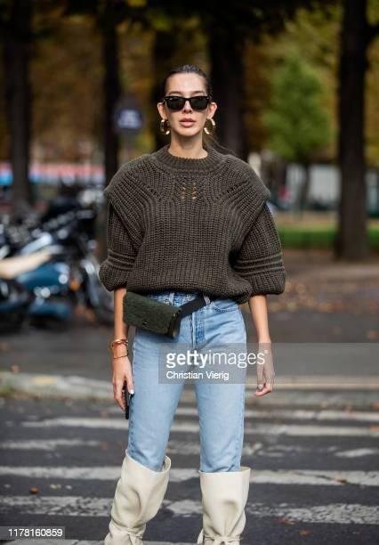 Estelle Pigault wearing olive knit, denim jeans, belt bag, creme white boots seen outside Akris during Paris Fashion Week Womenswear Spring Summer...