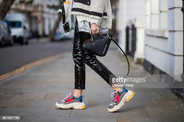 Estelle Pigault wearing Sacai jacket black vinyl pants Saint Laurent Balenciaga bag Balenciaga sneaker Prada tshirt during London Fashion Week Men's...