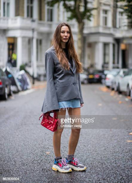 Estelle Pigault wearing vintage denim mini skirt a grey blazer with wide sleeves Milo Maria red Balenciaga mini bag Balenciaga Triple S sneakers on...