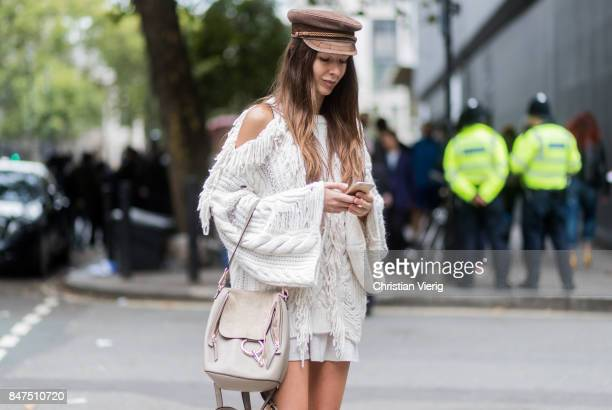 Estelle Pigault writting a text message wearing a white knit Chloe bag slippers socks flat cap during London Fashion Week September 2017 outside...