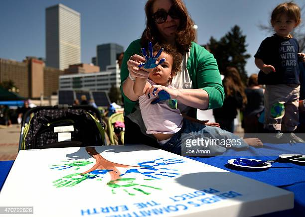 Estelle Reid 2 watching her blue hand after Sarah Reid put her print on the earth tree art work being made by Denver Environmental Health during...