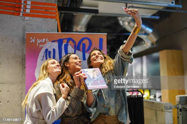 Estelle Sabathier Marine Lorphelin and Laury Thilleman take a selfie during the launch event for Laury Thilleman's book 30 jours pour être au TOP at...
