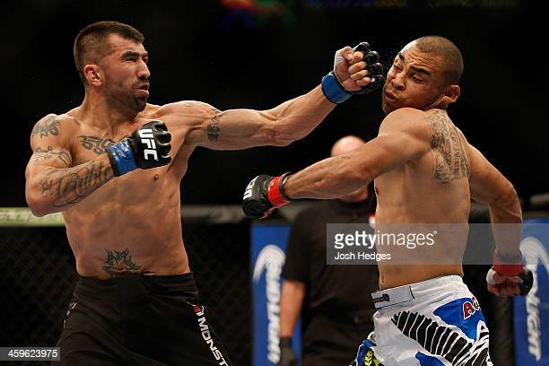 Estevan Payan punches Robbie Peralta in their featherweight bout during the UFC 168 event at the MGM Grand Garden Arena on December 28, 2013 in Las...