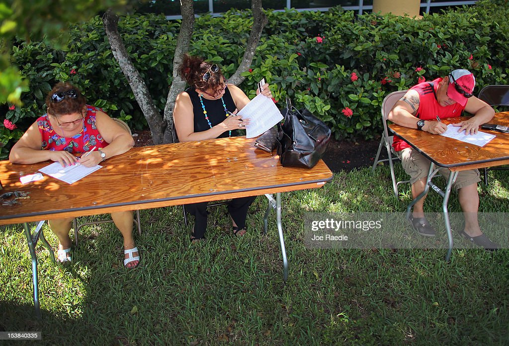 Esthel Otero, Roraina Campos and Luis Arencibia fill out their voter registration forms at the Miami-Dade Elections Department on the final day for them to register to vote in the upcoming elections on October 9, 2012 in Miami, Florida. The Republicans and Democrats are battling it out for the election, less than a month away.