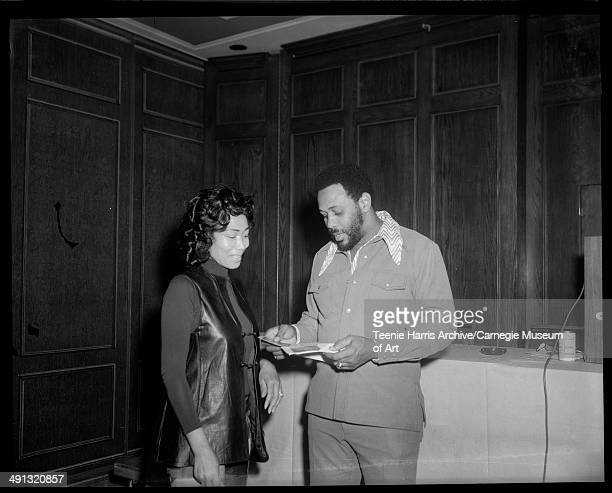 Esther Austin and Willie Stargell looking at book in wood paneled room with Sickle Cell Anemia donation can on table in background Pittsburgh...