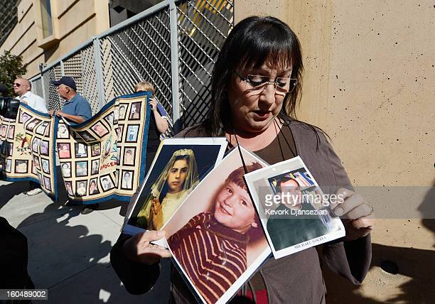 Esther Millar holds up pictures of Vicki and Mary who she says were victims of sexual abuse by a priest in the Catholic Archdiocese of Los Angeles...