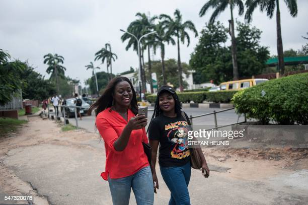 Esther Mustapha and her friend Oyinbecks Olajide use the Pokemon Go application on their mobile on the campus grounds of the University of Lagos on...