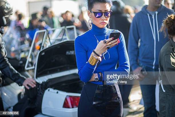 Esther Quek looks on her smartphone during the Paris Fashion Week Womenswear Spring/Summer 2016 on October 4 2015 in Paris France