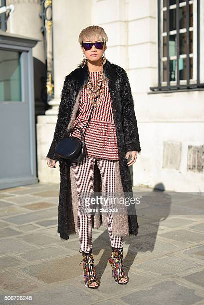 Esther Quek poses wearing Victoria Beckam top and pants Loewe bag and Giuseppe Zanotti shoes before the Miu Miu presentation at Place Beauvau during...