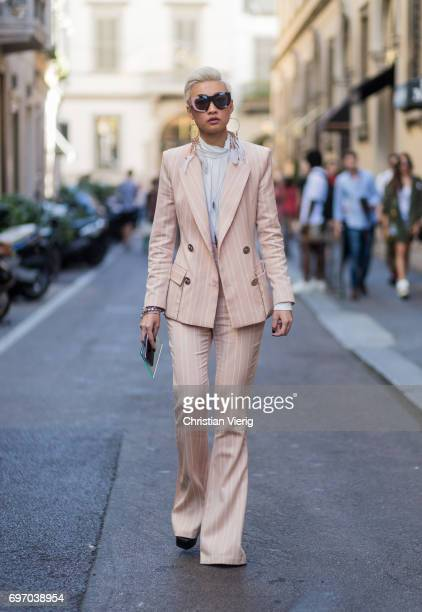 Esther Quek wearing a salmon coloured suit is seen outside Versace during Milan Men's Fashion Week Spring/Summer 2018 on June 17 2017 in Milan Italy