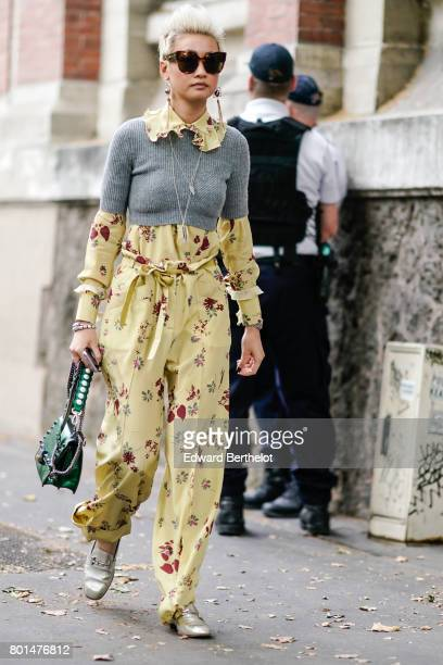 Esther Quek wears sunglasses a gray wool pull over a yellow flower print outfit and a green bag outside the Paul Smith show during Paris Fashion Week...