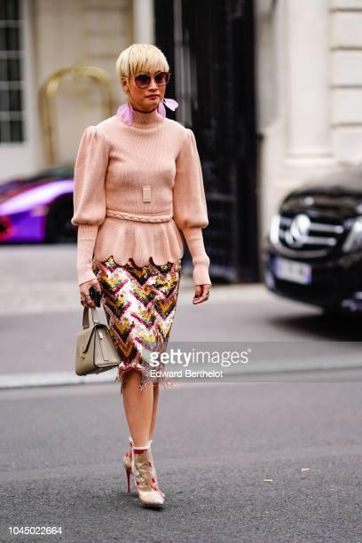 Esther Quek wears sunglasses a pink wool pullover a skirt earrings outside Miu Miu during Paris Fashion Week Womenswear Spring/Summer 2019 on October...