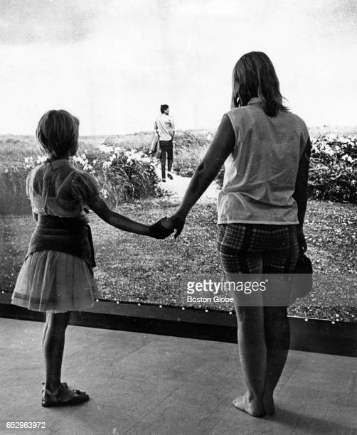 Esther Von Laue left and Madeleine Von Laue hold hands while looking at a photograph of John F Kennedy at the traveling John F Kennedy Library...