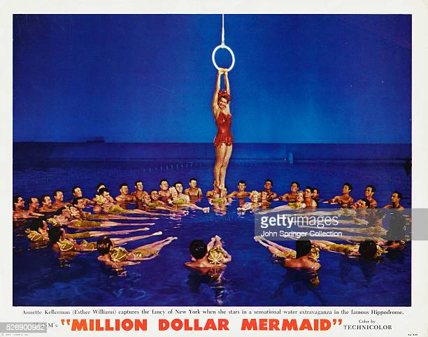 Esther Williams portraying Australian swimmer Annette Kellerman hangs from a ring above a circle of synchronized swimmers