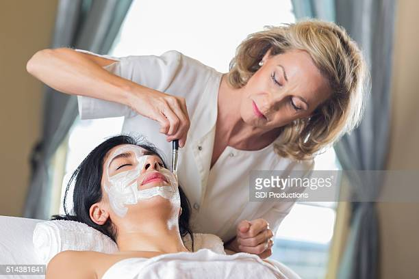 Esthetician applying face mask cream to customer's face in spa