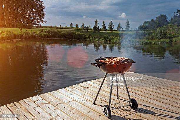 Estonia, barbecue grill on wooden platform by lake