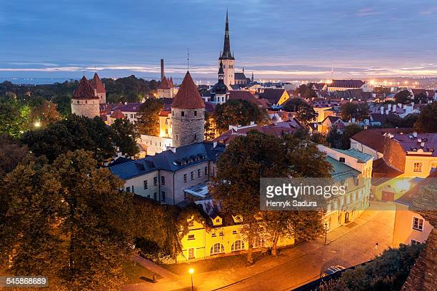 Estonia, Tallinn, St. Olafs Church and surrounding cityscape at dusk