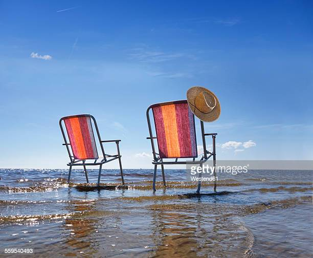 Estonia, two folding chairs standing in water at shore