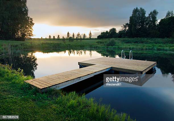 Estonia, wooden floating platform by lake at sunset
